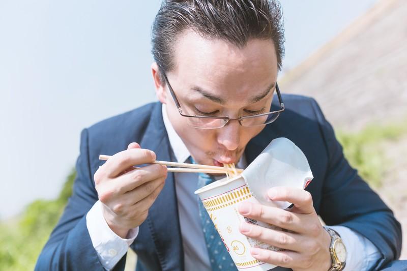 眼鏡男子がラーメンを食べる